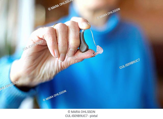 Senior woman holding hearing aid, close-up