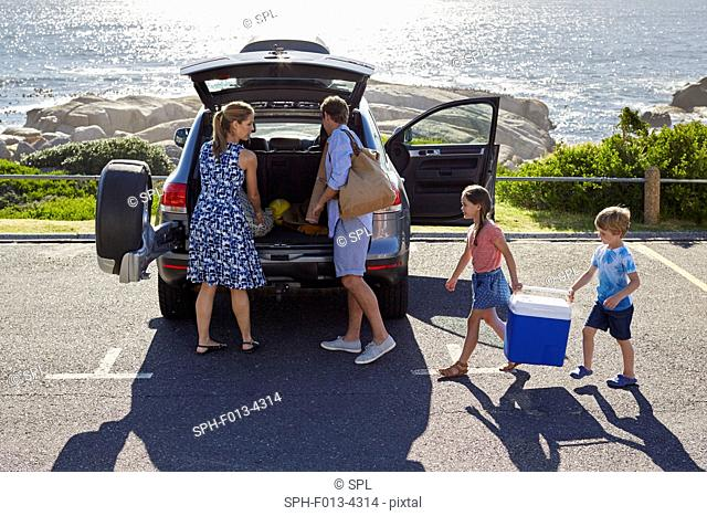 MODEL RELEASED. Family with two children unpacking the car by the beach