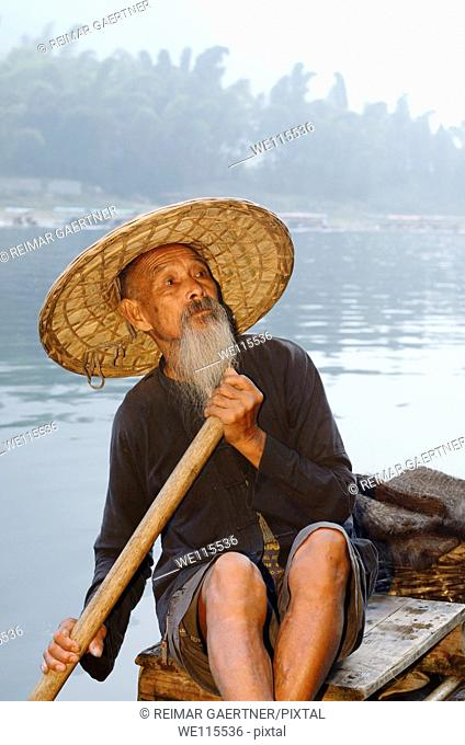 Proud Cormorant fisherman on a bamboo raft on the Li river with Karst mountain peaks China