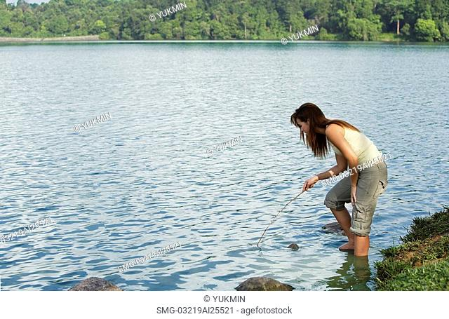 Young woman playing with stick in lake