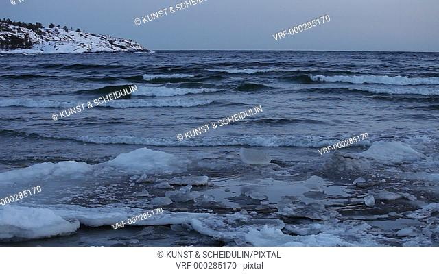 Waves are rolling onto the beach. It's the blue hour on a winter day at the swedish High Coast / Höga Kusten. Smitingen, Härnösand, Västernorrland, Sweden