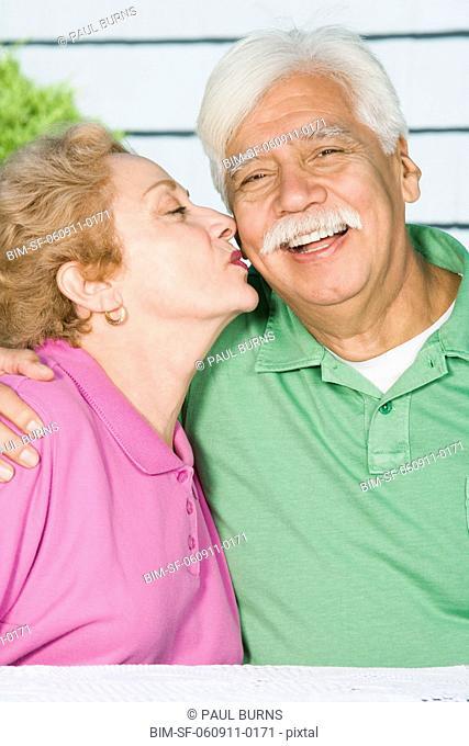 Senior Hispanic woman kissing husbandÆs cheek