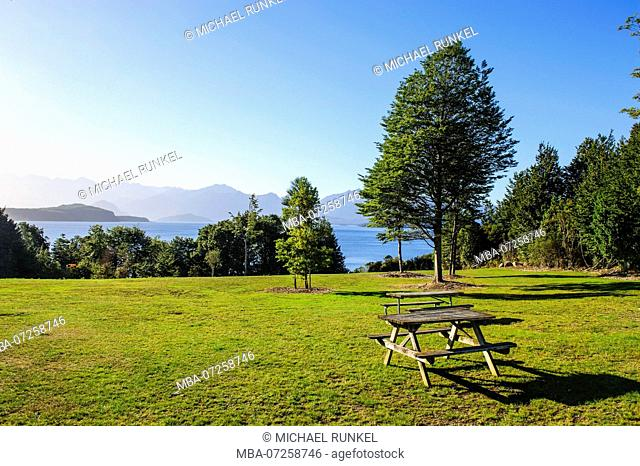 Picknick table on a lawn above lake Ta Anau, Manapouri, South Island, New Zealand