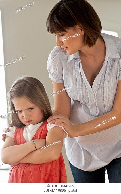 Mid adult woman consoling sulking daughter, portrait