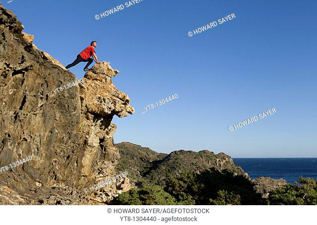 Man leaning on rocks at Cap de Creus in Catalonia, Spain