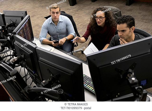 Young traders at meeting in front of computer monitors