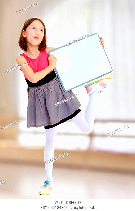 Emotional a small, thin girl, holding a front of a white poster. She stands on one leg. In a room with a large semi-circular window