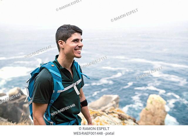 Smiling man with a backpack in front of the sea at the coast