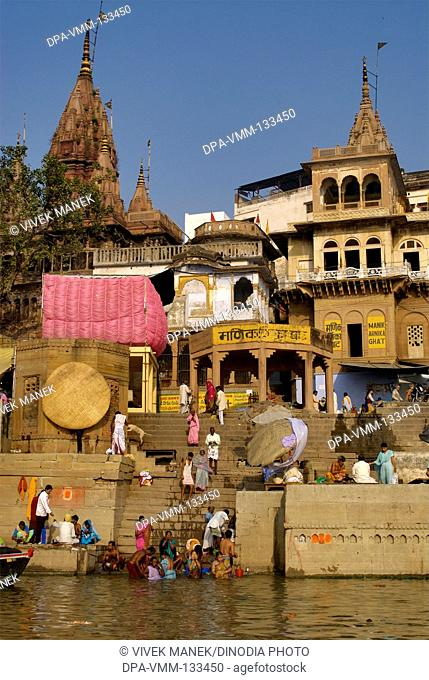 People bathing in holy Ganga river; Manikarnika Ghat ; Varanasi ; Uttar Pradesh ; India