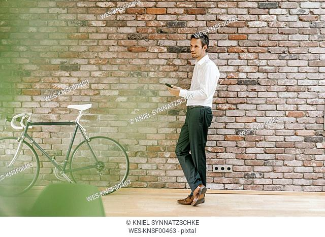Businessman with bicycle and cell phone at brick wall