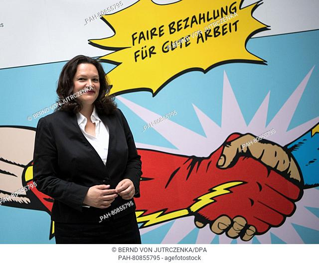 German Minister of Labor Affairs Andrea Nahles poses in front of a poster from her ministry written with 'Fair pay for good work' on the occasion of a press...