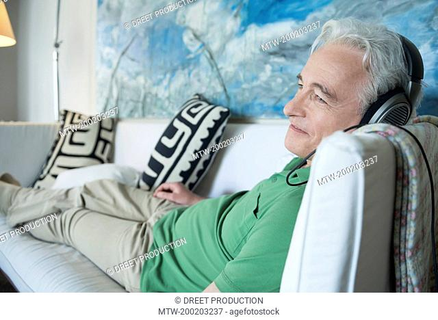 Mature man with headset sitting on couch, smiling