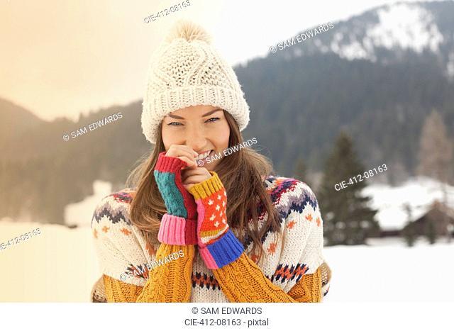 Portrait of smiling woman wearing knit hat in snowy field