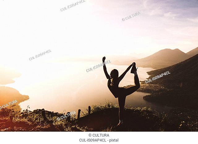 Silhouetted view of young woman posing at sunset above Lake Atitlan, Guatemala