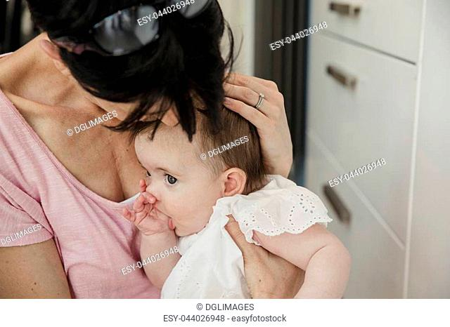 Close-up of a mid adult mother holding her baby daughter close and comforting her as she sucks her thumb. They are wearing casual clothing an sitting down
