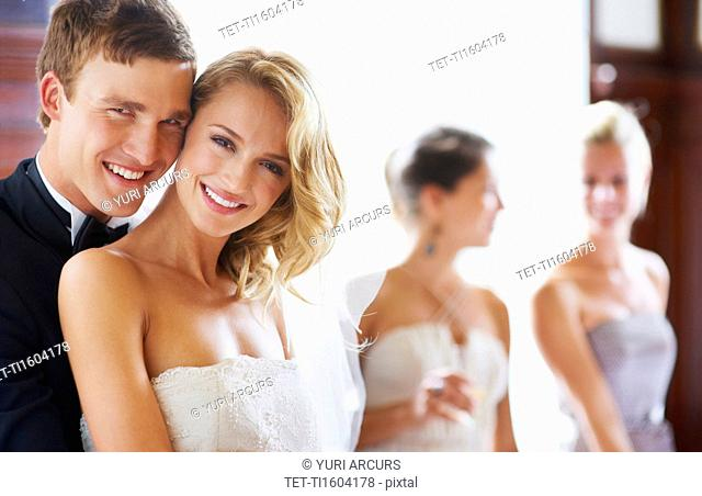 Portrait of newly wed couple, bridesmaids in background