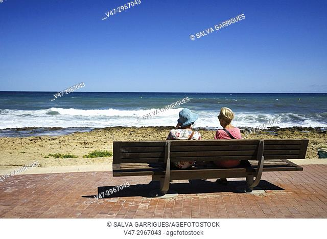 Two two women watching the sea on the beach of Javea, Alicante, Valencia, Spain, Europe