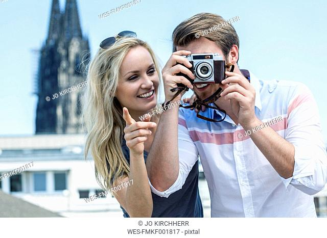 Germany, Cologne, young couple taking a picture with camera