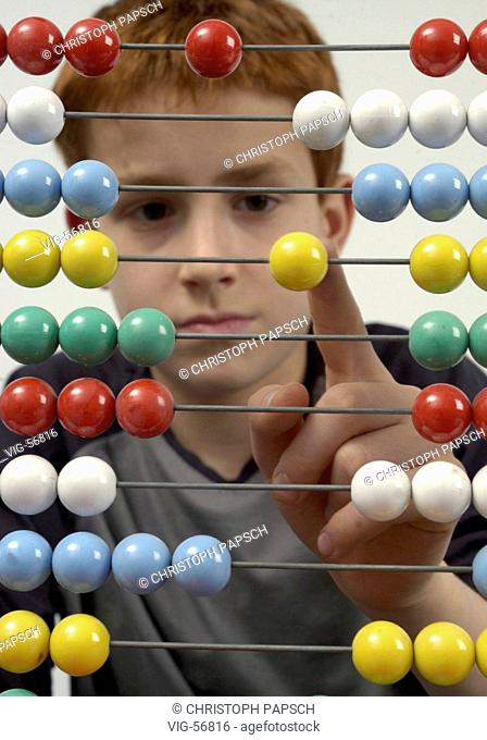 Left-handed boy calculating with an abacus. - BONN, GERMANY, 15/04/2004