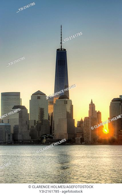 The sun rises over lower Manhattan as the Freedom Tower 1 World Trade Center stands tall nearby in the World Trade Center complex, in New York City, New York