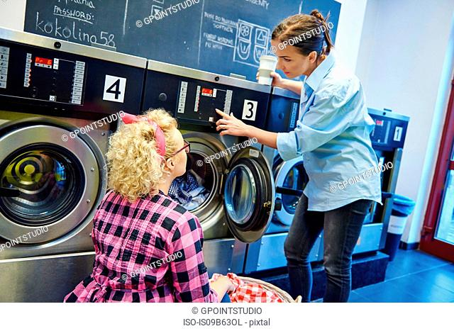 Laundrette business owner showing woman washing machine control panel