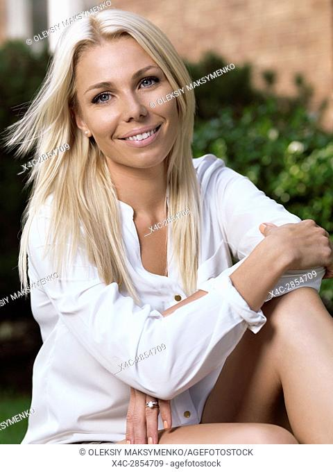 Outdoor portrait of a young smiling caucasian woman with blond hair in her thirties sitting in front of a house