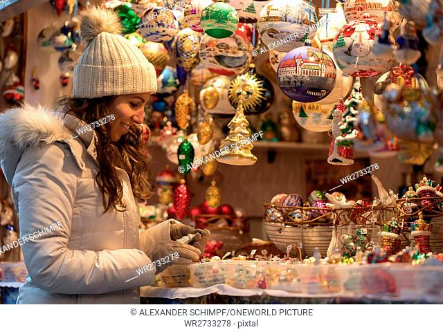 Switzerland, Basel city, Young woman in winter clothes looking at Christmas decorations of a Christmas market stand, on the Christmas market