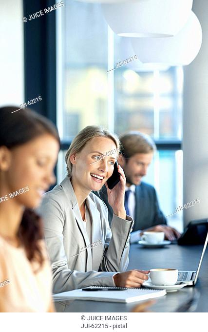 Smiling businesswoman talking on cell phone in coffee shop