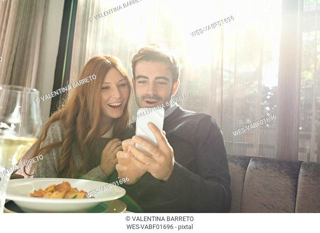 Happy couple looking at cell phone in a restaurant