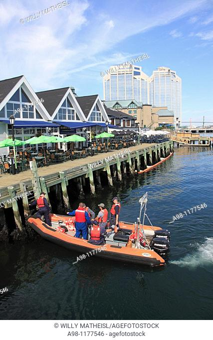 workers mooring boat at the downtown Harbour Walk of Halifax, Nova Scotia, Canada, North America