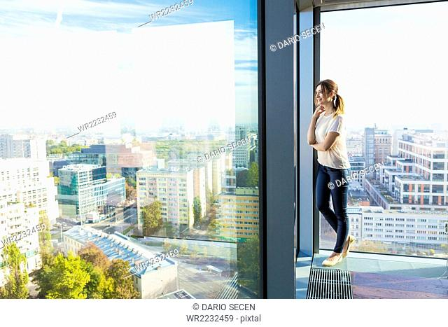 Woman in apartment looking through window