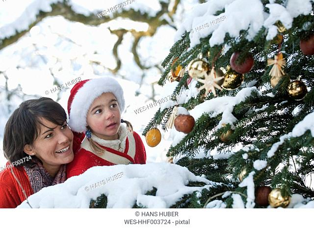 Austria, Salzburg Country, Flachau, Young mother and daughter looking at christmas tree