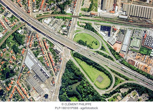 Aerial view over ribbon building and highway interchange / motorway interchange with slip roads leading to industrial estate