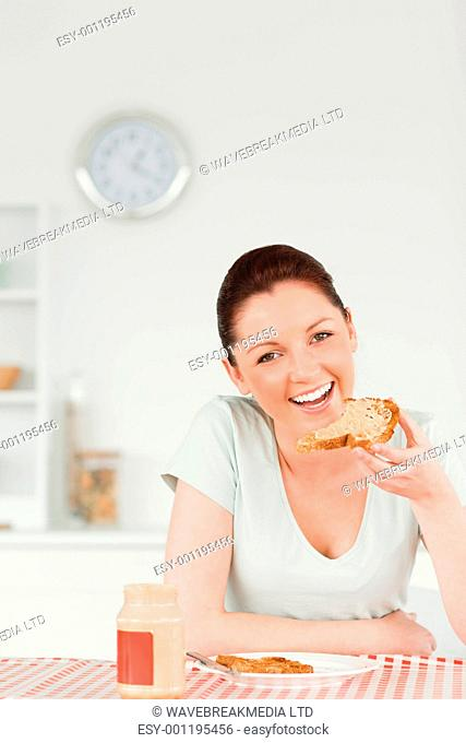 Good looking female preparing a slice of bread and marmalade in the kitchen