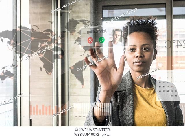 Young woman receiving a call on glass wall with world map in office