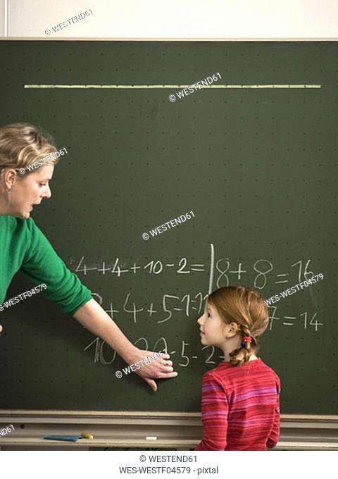 Teacher explaining arithmetic problem to girl