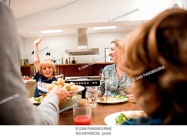 Family at the dinner table with son raising arm requesting more food