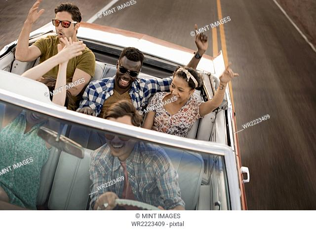 A group of friends in a red open top convertable classic car on a road trip