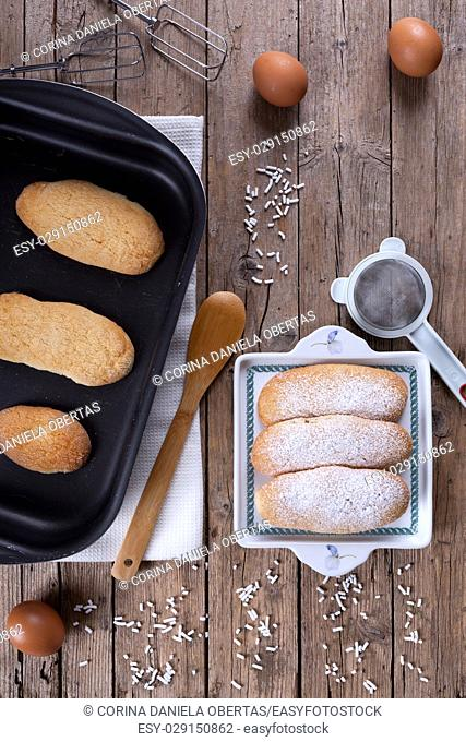 Overhead shot of baking pan with fresh baked ladyfingers (italian savoiardi biscuits) on table with kitchen utensils and eggs