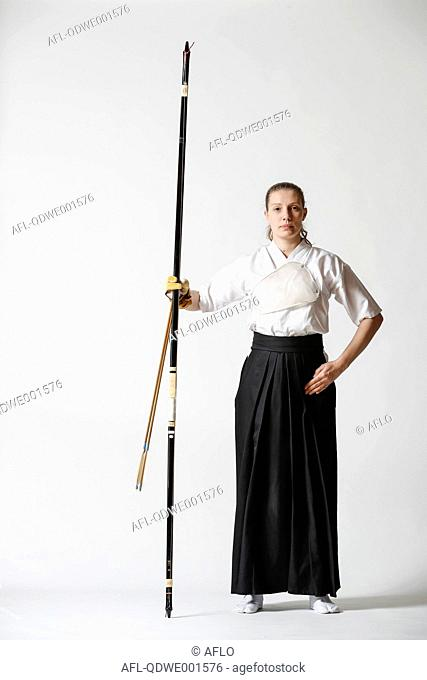 Caucasian woman practicing traditional Kyudo Japanese archery on white background