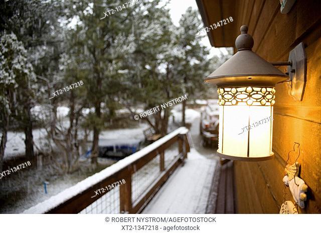 Porch light shining during an evening snow in colorado