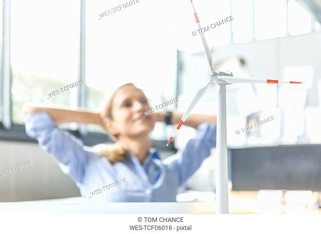 Wind turbine model and woman in background in office