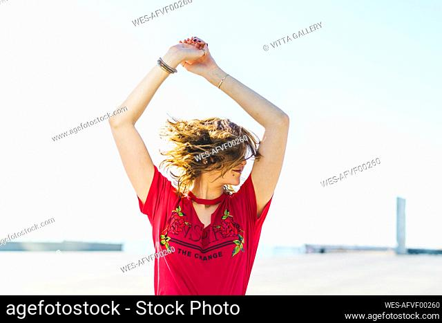 Happy young woman outdoors shaking her hair