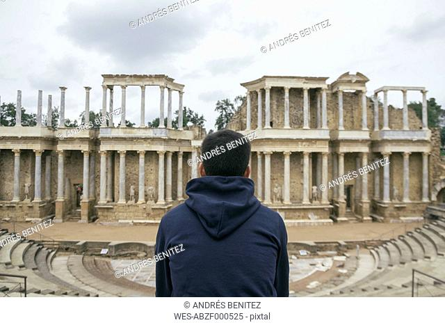 Spain, Merida, back view of man sitting in front of Roman theater