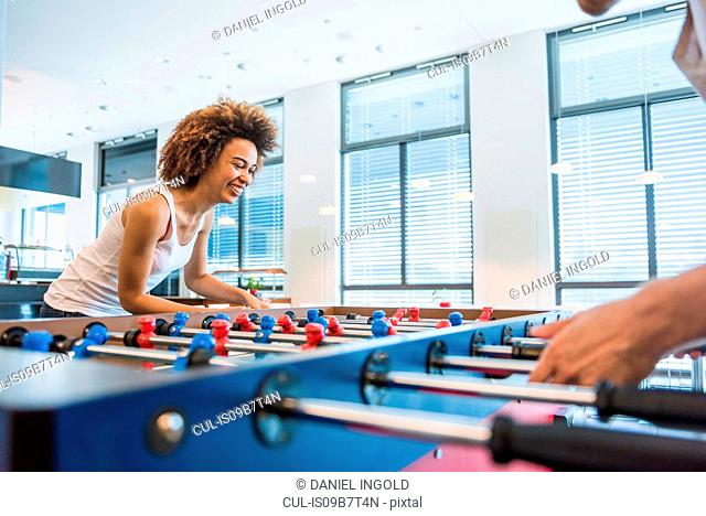 Young woman and boyfriend playing table football