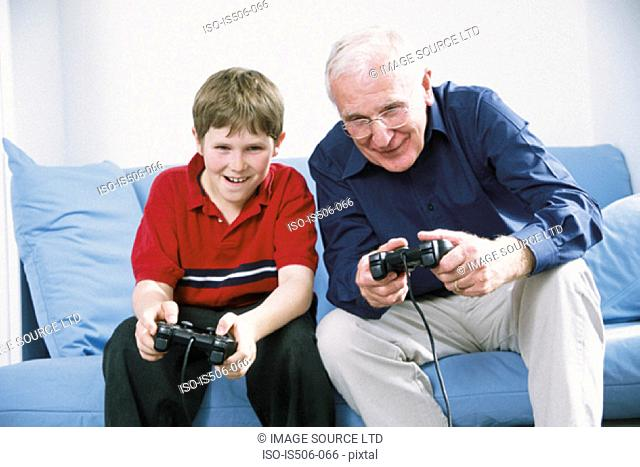 Grandfather and grandson playing with computer game