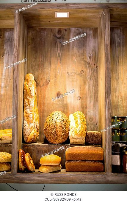 Fresh loaves, bread buns and baguette in bakery tray