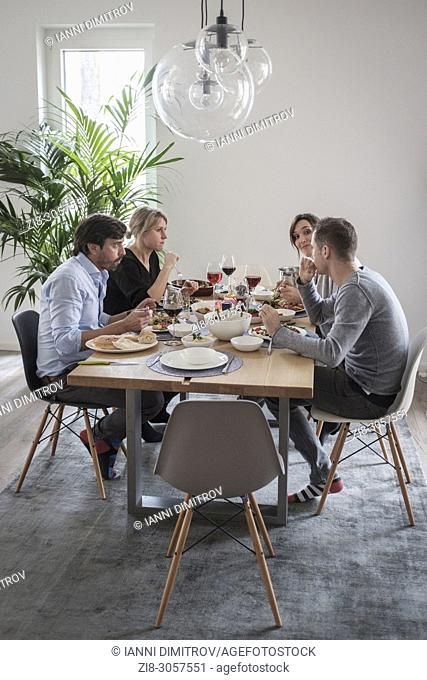 Group of friends casually snacking on a selection of food while laughing and enjoying themselves
