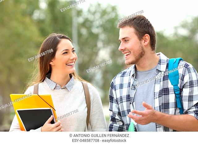 Two happy students walking towards camera and talking in a park or university campus