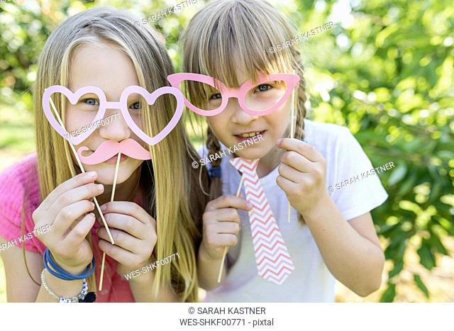 Two playful sisters in garden